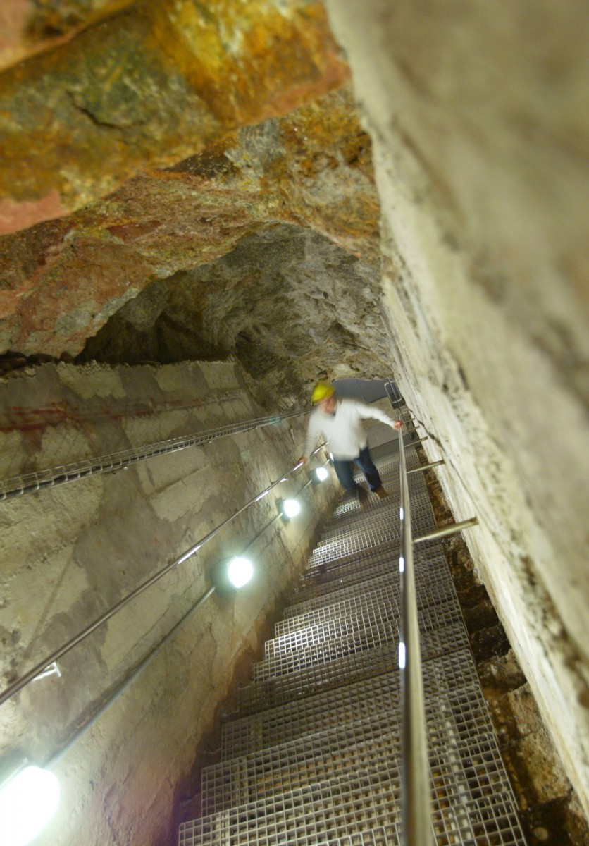 Visitor climbing the escape steps in Porthcurno's World War 2 tunnels