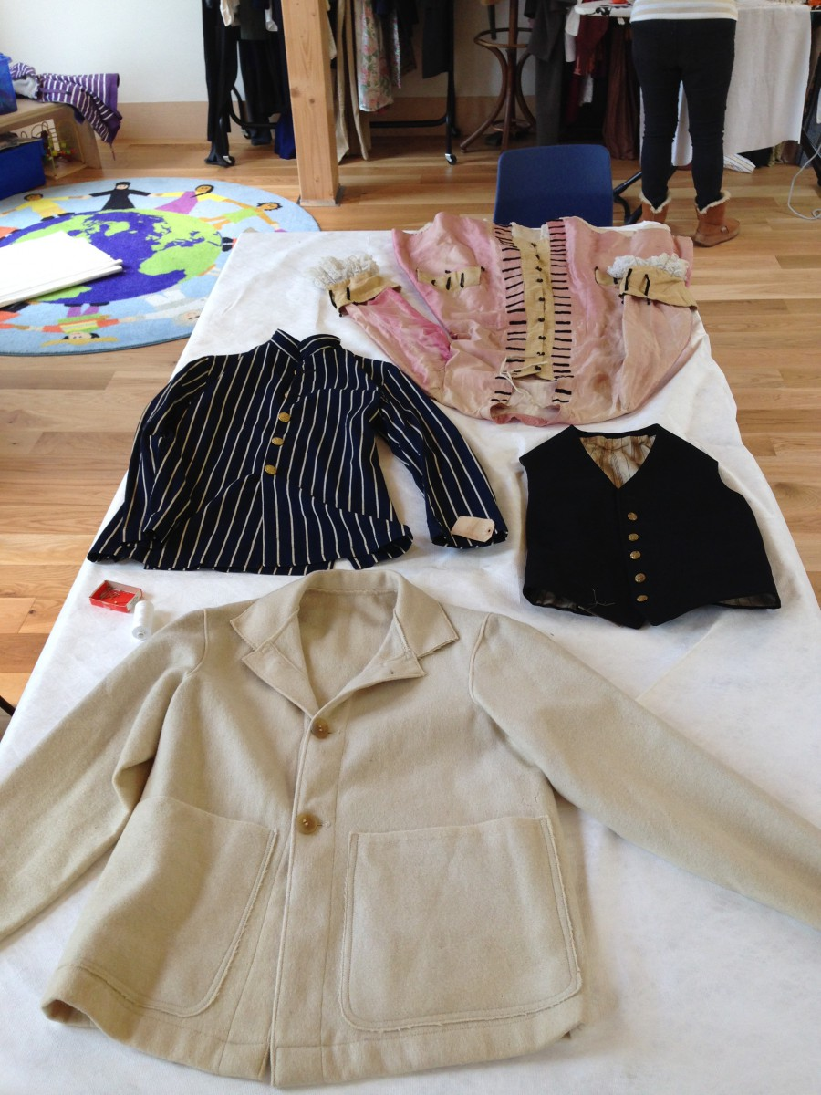 Displaying Textiles - Here we have laid out a number of jackets for re-display. We have covered the table with Tyveck sheet which is a synthetic material and helps to protect the fibers and embellishment from damage.