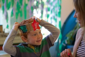 Ligttle boy wearing colourful crown in children's party