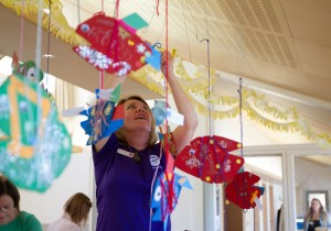 Museum staff member hangs sparkly fish decorations from the ceiling in children's party