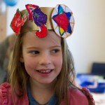 A little girl wear a colourful paper party crown for a children's party