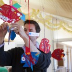 A parent helps to hang fish decorations for a chicldren's party