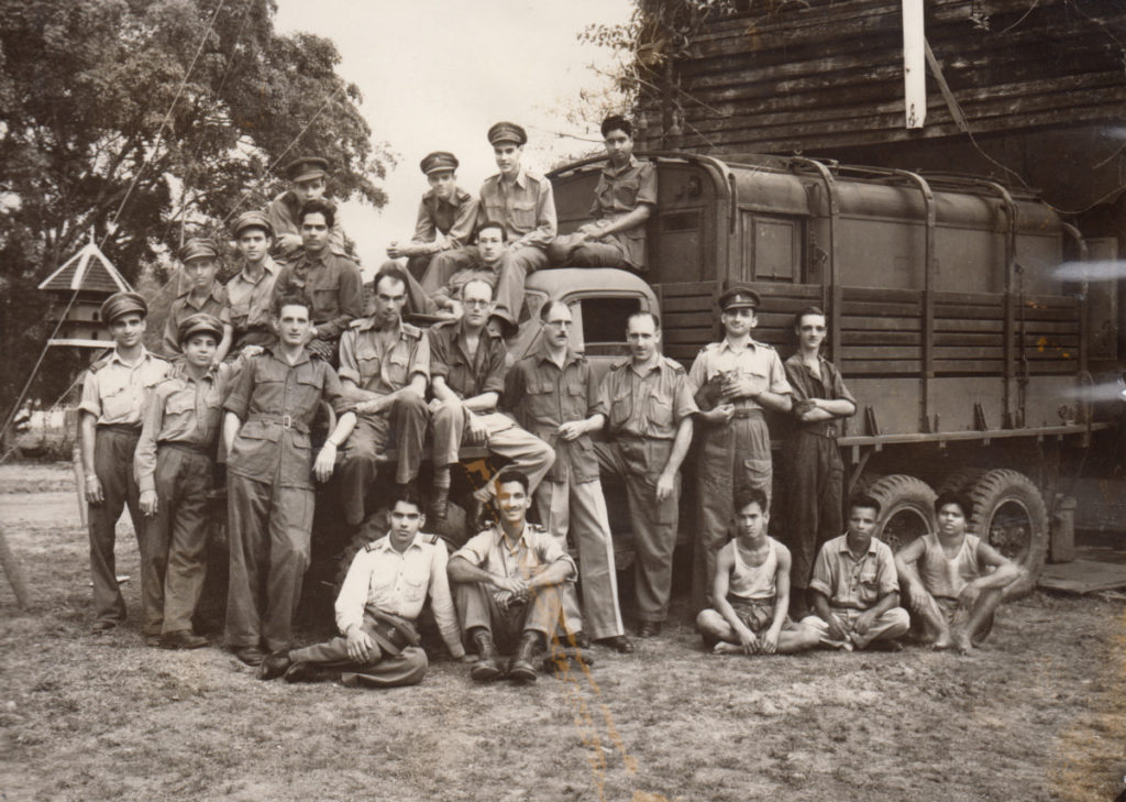 Sepia photograph of World War Two personnel standing in front of and on a truck.