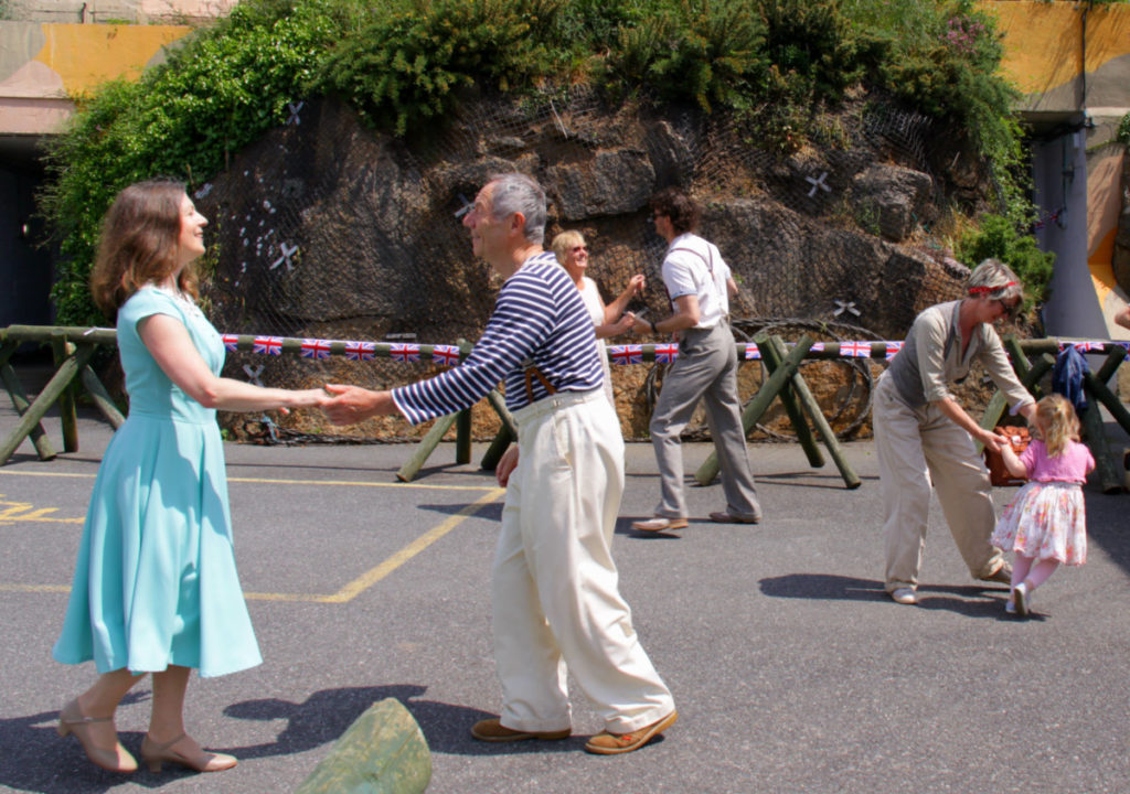 Outdoor photograph of swing dancers at museum launch event, dancing for members of the public in front of unique World War Two Tunnels