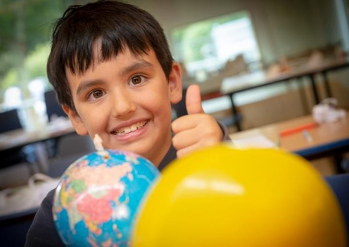 A photo of a ten-year-old boy exploring a rotating model of the solar system.