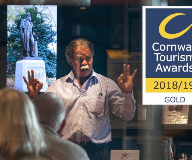 Photograph of Front of House staff at Telegraph Museum Porthcurno giving a demonstration within the public gallery with logo for Cornwall Tourism Awards Gold winner 2018 to 2019.