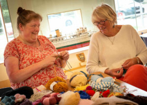 Warming photograph of two female museum volunteers surrounded by multi coloured balls of wool and knitting projects.