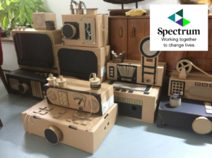Photograph of family activity for autism inclusion called Cardboard Communication Station, showing cardboard play engineering boxes which represent the historic telegraph communication system, with autism charity logo, Spectrum.