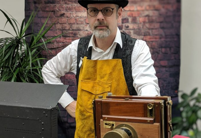 Photograph of Si Colgan, Tintype photographer, at Telegraph Museum Porthcurno with photographic set up.