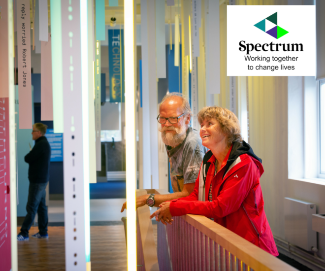 A colour photograph of visitors exploring the exhibits in the museum galleries, with autism charity logo, Spectrum.