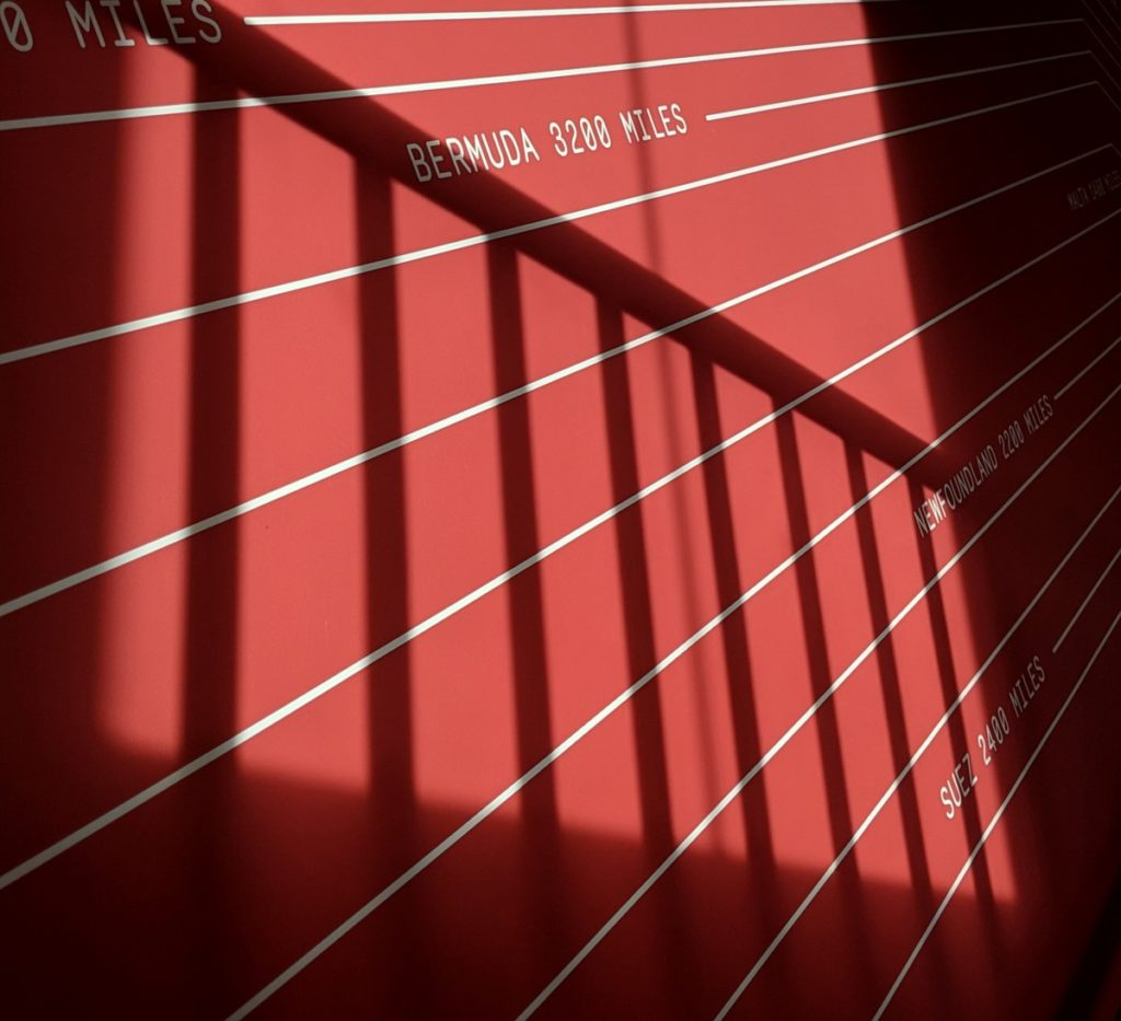 Dynamic colour photograph of pink museum wall with white global locations relative to the historic telegraph station in Porthcurno, with striking shadows and light from opposite window and stairs.