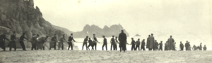 Historic photograph showing Porthcurno beach and Logans Rock with cable laying group.