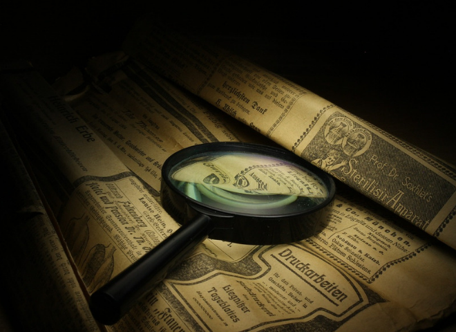 Magnifying glass on a newspaper.