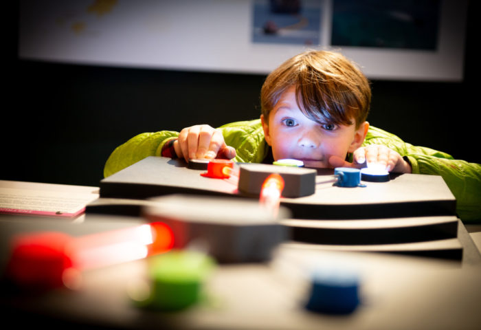 Close up photograph of boy using a museum interactive to learn about fibre optics and methods of light splitting to transmit large packages of data.