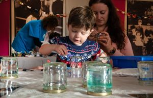 Colour photograph of family friendly things to do at the Telegraph Museum Porthcurno, featuring child and parent enjoying make and take activity in Clore Learning Space.
