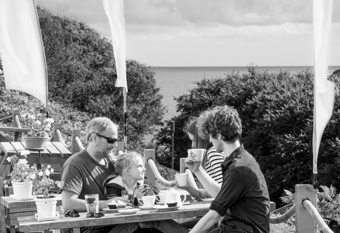 Amazing things to do in Porthcurno, Cornwall, black and white photograph showing family with children eating and drinking at the Telegrapher's Tea Room at the Telegraph Museum Porthcurno.